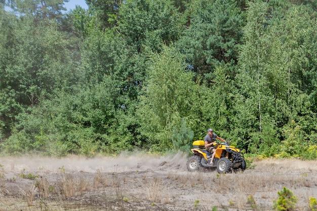 Mężczyzna jedzie na żółtym quadzie atv pojazd terenowy po piaszczystym lesie