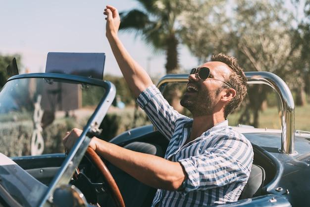 Mężczyzna jedzie odwracalnego rocznika samochód
