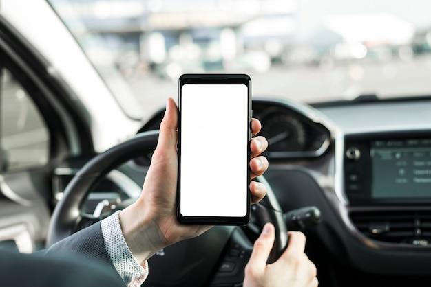 Mężczyzna jedzie samochód pokazując mobilny pusty biały ekran wyświetlania