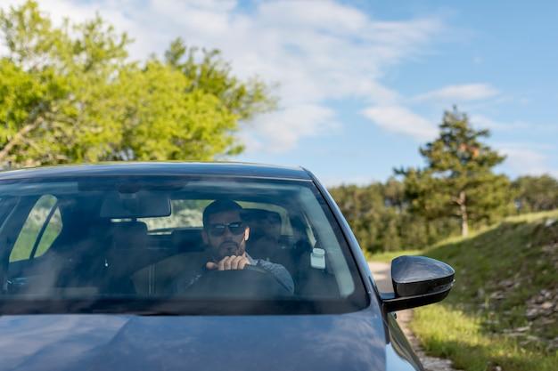 Mężczyzna jedzie samochód z okularami przeciwsłonecznymi