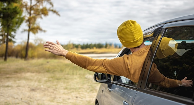 Mężczyzna jedzie samochodem wzdłuż rzeki i lasu, ciesząc się ciszą, słońcem i piękną jesienną przyrodą
