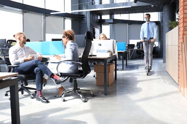 Mężczyzna jedzie skuterem w profilaktycznej masce medycznej w epidemii w nowoczesnym biurze na otwartej przestrzeni, koledzy w tle. grupa postępowych ludzi biznesu pracujących razem na starcie.