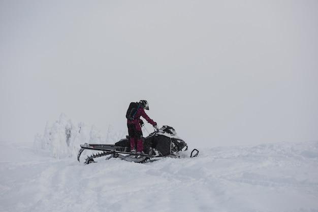 Mężczyzna jedzie skutery śnieżne w śnieżnych alps