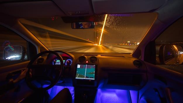Mężczyzna jedzie z gps na miasto nocą. widok od wewnątrz
