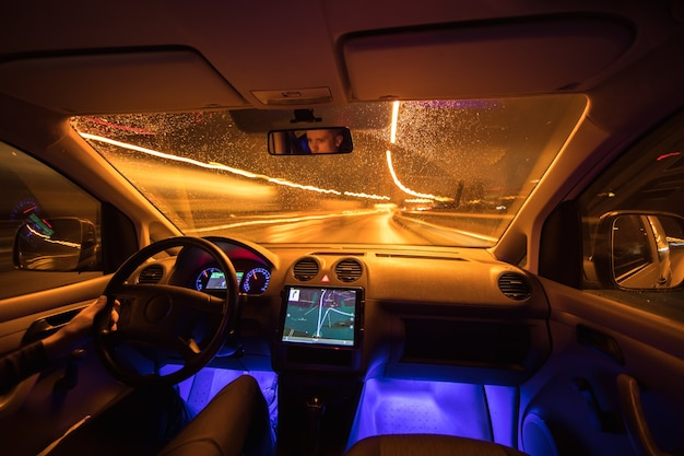 Mężczyzna jedzie z gps na nocnej drodze. widok od wewnątrz. szeroki kąt