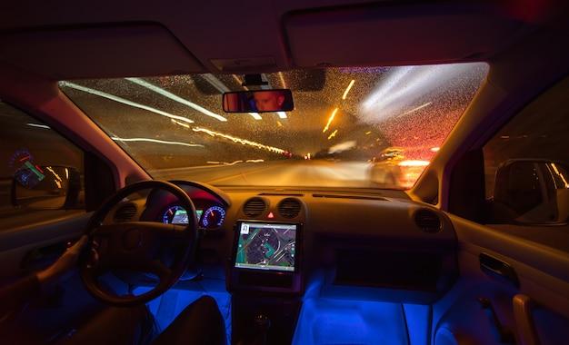 Mężczyzna jedzie z mapą po deszczowej drodze. wieczorna pora nocna. widok od wewnątrz