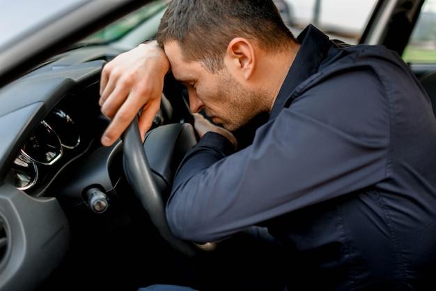 Mężczyzna jest bardzo zmęczony prowadzeniem samochodu i spaniem na kierownicy
