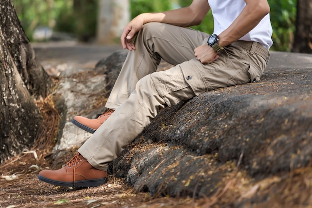 Mężczyzna jest ubranym brown ładunków spodnia i obsiadanie w natura parku