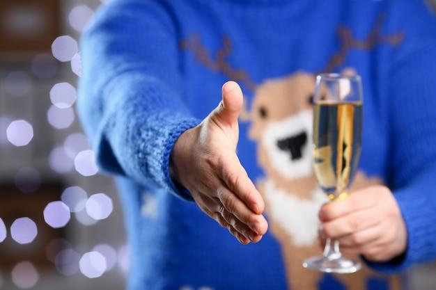 Mężczyzna jest ubranym ciepłego błękitnego jeleniego puloweru chwyt w ręki szampańskiej czara daje ręce jak cześć w biurze z rozjarzoną girlandą w tła zbliżeniu. pozytywny przyjaciel mile widziany oferta mediacji na strajk
