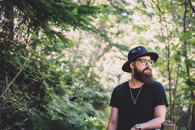 Mężczyzna jest ubranym czarnego kapelusz w lesie
