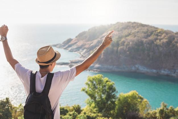 Mężczyzna jest ubranym kapelusz trzyma jego rękę szczęśliwą. mężczyzna azjatycki turysta spójrz na góry i morze przed zachodem słońca. dla aktywności styl życia na zewnątrz wolność lub podróż turystyka inspiracja backpacker turysta covid 19