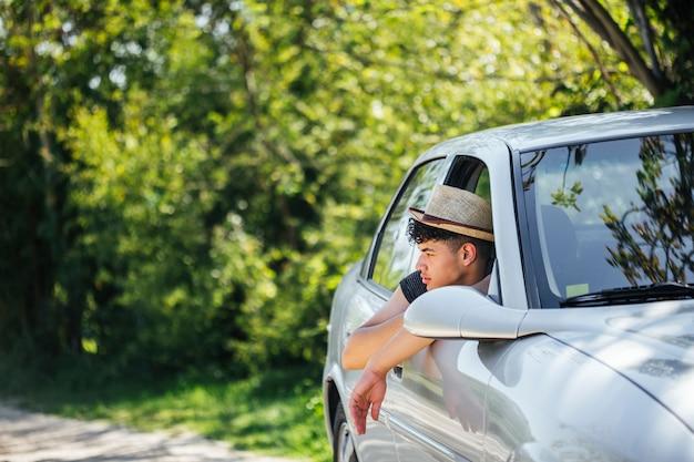 Mężczyzna jest ubranym kapeluszową przyglądającą naturę przez samochodowego okno