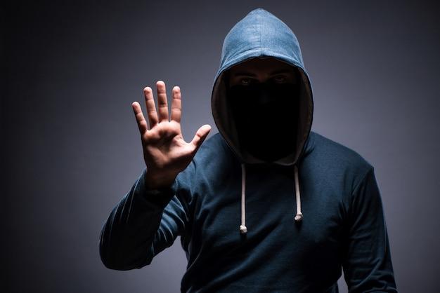 Mężczyzna jest ubranym kapiszon w ciemnym pokoju