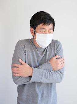 Mężczyzna jest ubranym maskę ochronną jest zimny