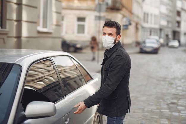 Mężczyzna jest ubranym maskę ochronną samochodem