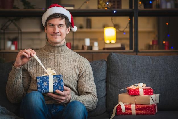 Mężczyzna jest ubranym santa kapeluszowego otwarcia błękita prezent