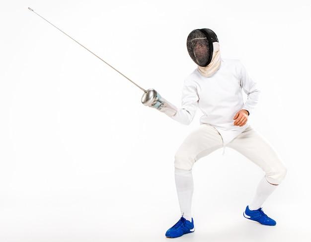 Mężczyzna jest ubranym szermierczego kostium ćwiczy z kordzikiem przeciw szarość
