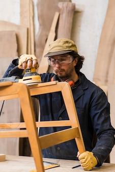 Mężczyzna jest ubranym zbawczych eyeglasses pracuje z orbitacyjnymi sanders na drewnianych meblach