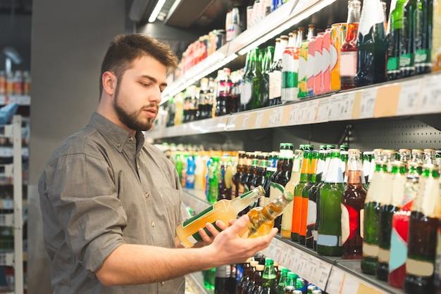 Mężczyzna jest w dziale alkoholowym w supermarkecie z dwiema butelkami w rękach, patrzy na etykiety i czyta