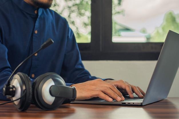 Mężczyzna jest wsparciem online słuchawek call center w domu, mężczyźni pracujący przy użyciu komputerowej technologii online