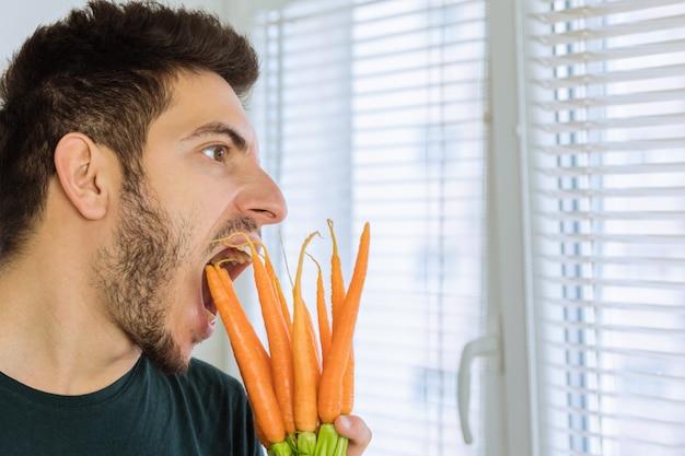 Mężczyzna jest zły i zdenerwowany, nie chce jeść warzyw. on chce jeść czekoladę.