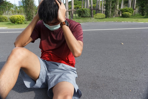 Mężczyzna jest zmęczony po treningu. mężczyzna sportowiec cierpi na ból głowy i zawroty głowy.