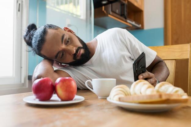 Mężczyzna jest zmęczony podczas spożywania śniadania