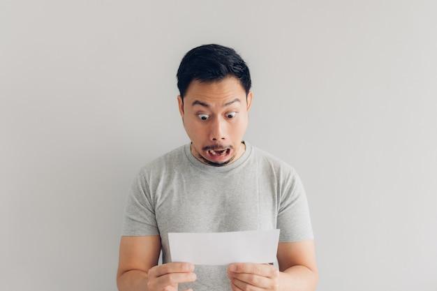 Mężczyzna jest zszokowany i zaskoczony białą wiadomością pocztową lub rachunkiem.