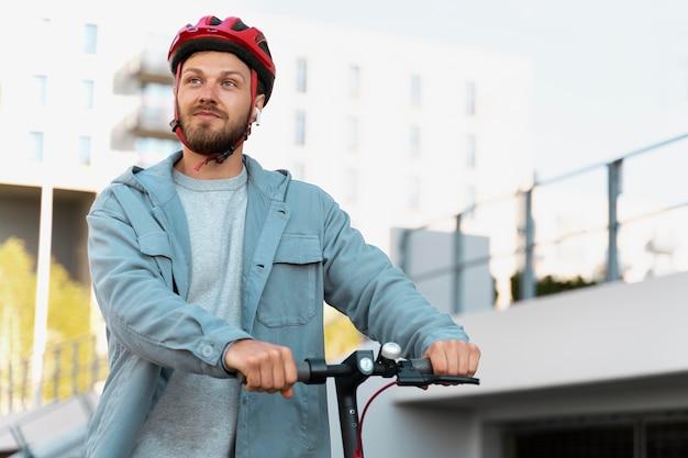 Mężczyzna jeżdżący ekologiczną hulajnogą po mieście