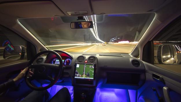 Mężczyzna jeździ autostradą miejską z nawigacją. wieczorna pora nocna