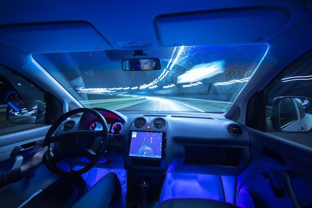 Mężczyzna jeździ samochodem z gps w nocnym mieście. szeroki kąt