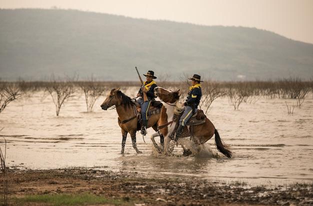 Mężczyzna jeździecki koń na polu podczas zmierzchu przy brzeg rzeki