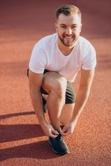 Mężczyzna jogger wiązany sznurowadłami na stadionie