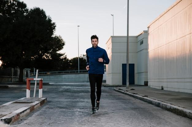 Mężczyzna jogging na ulicy w zmierzchu