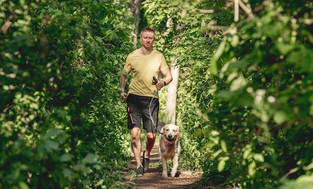 Mężczyzna jogging z psem w drewnie