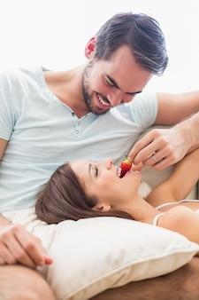 Mężczyzna karmi jego dziewczyny truskawki