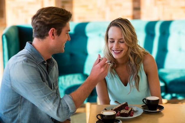 Mężczyzna karmienia tort kobieta w kawiarni