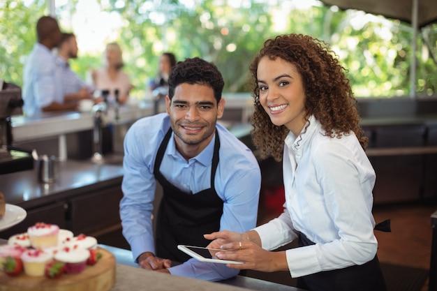 Mężczyzna kelner i kobieta kelnerka z cyfrowego tabletu