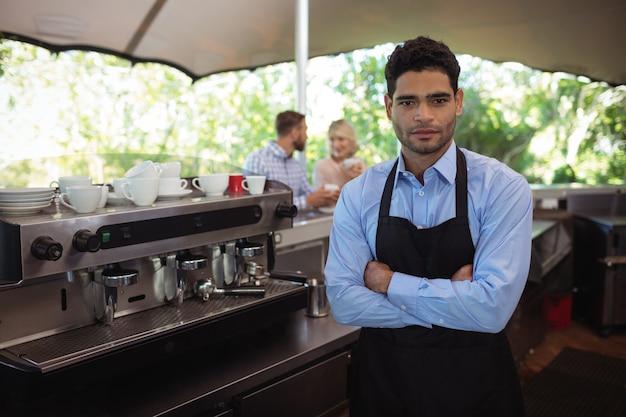 Mężczyzna kelner stojący z rękami skrzyżowanymi w restauracji