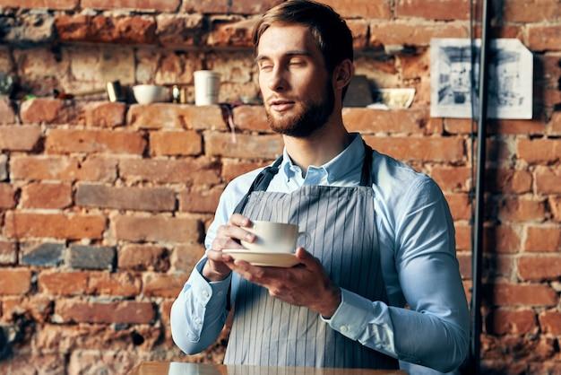 Mężczyzna kelner trzymający filiżankę kawy w kawiarni