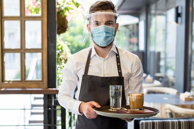 Mężczyzna kelner z maską