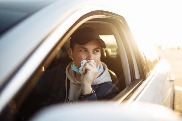 Mężczyzna kicha podczas prowadzenia samochodu podczas kwarantanny koronawirusa