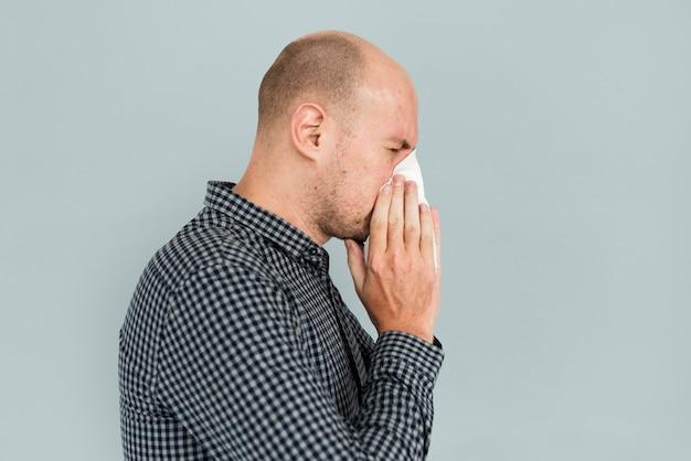 Mężczyzna kichający, wydmuchujący chorobę nosa