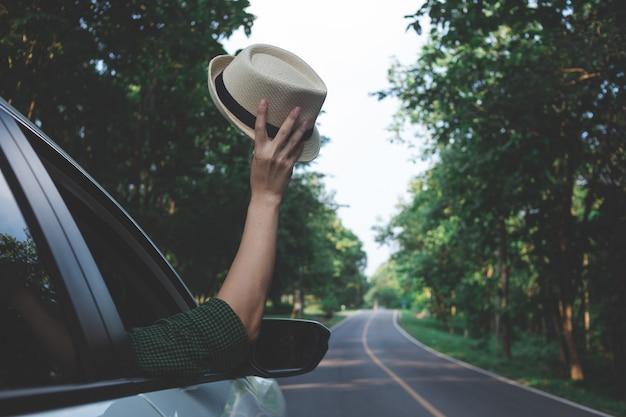 Mężczyzna kierowca czuje wiatr w dłoniach podczas jazdy na wsi.