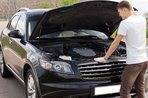 Mężczyzna kierowca lub mechanik stojący z maską, sprawdzający silnik swojego samochodu car