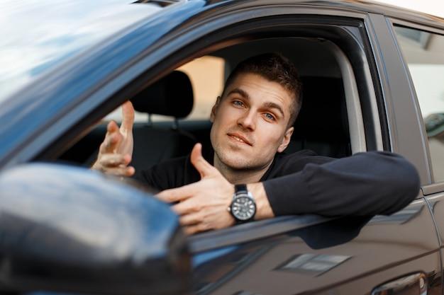 Mężczyzna kierowca macha rękami i zadaje pytanie. emocje zaskoczenia