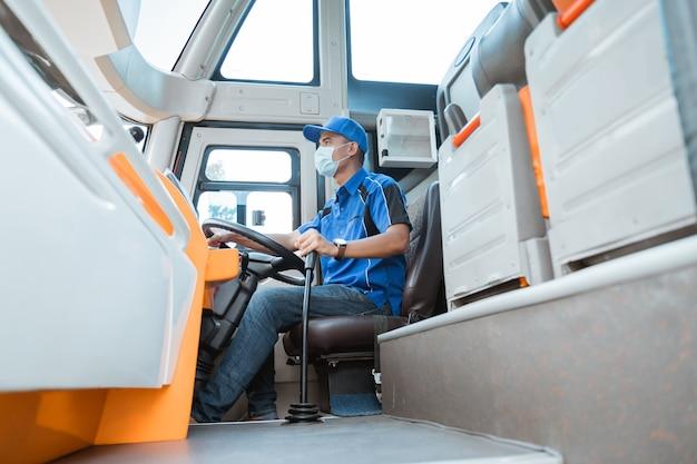 Mężczyzna kierowca w mundurze i masce, trzymając w autobusie kierownicę i dźwignię zmiany biegów