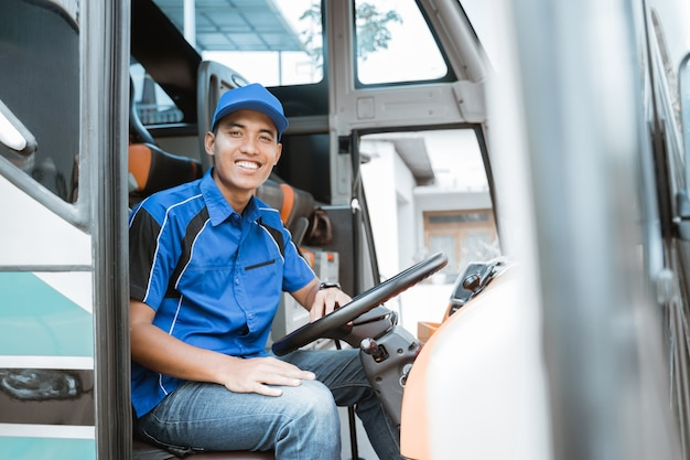 Mężczyzna kierowca w mundurze uśmiecha się siedząc za kierownicą autobusu