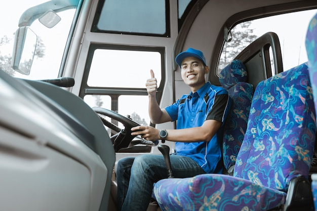 Mężczyzna kierowca w niebieskim mundurze uśmiecha się do kamery z podniesionymi kciukami siedząc w autobusie