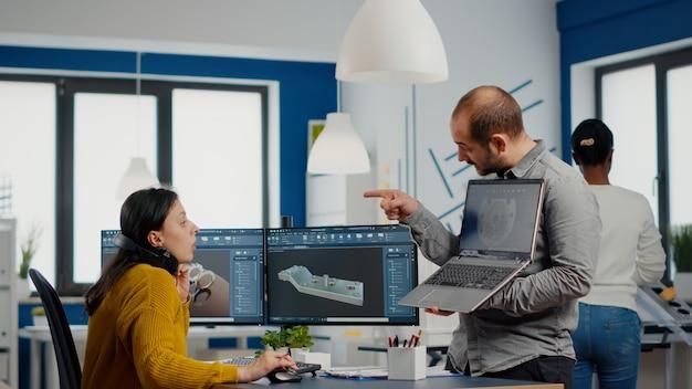 Mężczyzna kierownik projektu trzymający laptopa i wskazujący na wyświetlacz pokazujący kobietę inżynier przemysłow...